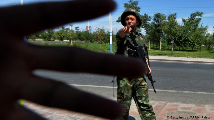 A hand blocks a camera in China's Xinjiang province