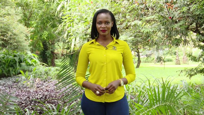 Sandrah Twinoburyo, Eco Africa presenter, in a yellow shirt surrounded by green leaves.