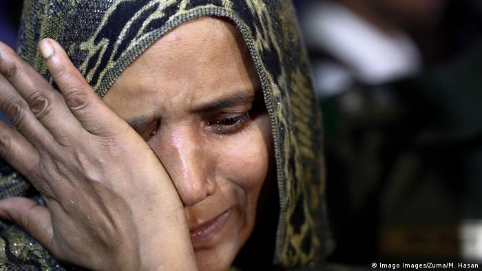 A Bangladeshi woman wiping tears from her eyes