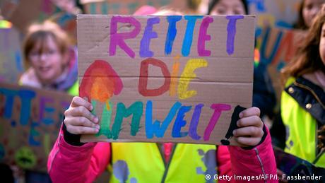 """Eine Demonstrantin hält ein Schild hoch, auf dem steht: """"Rettet die Umwelt""""."""