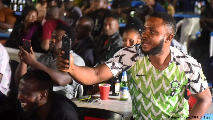 Young football fans in Nigeria with their smartphones