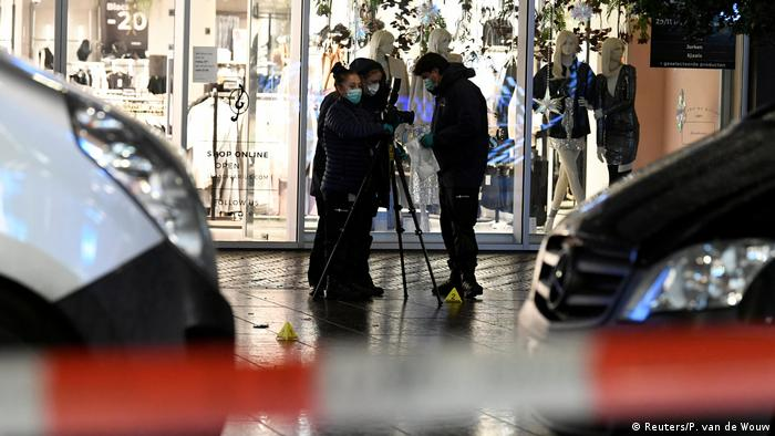 Forensics officers wearing black and face masks carry out work in front of a department store in The Hague.