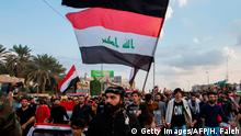 I29.11.2019 raqi protesters march with national flags and a Shiite Muslim flag reading in Arabic oh martyr Hussein during an anti-government demonstration in the southern Iraqi city of Basra on November 29, 2019. (Photo by Hussein FALEH / AFP) (Photo by HUSSEIN FALEH/AFP via Getty Images)