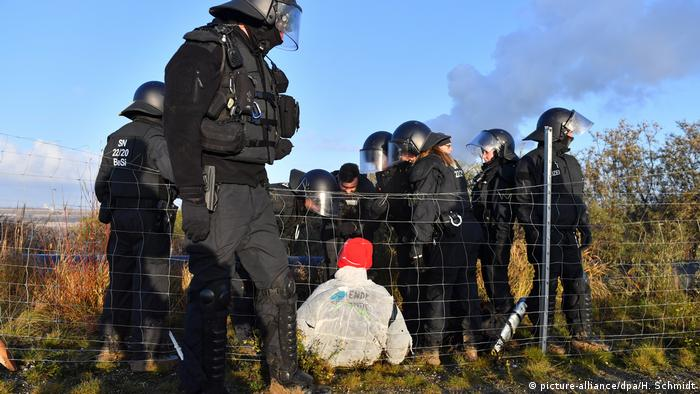 Police offers stand around a climate protester at the United Schleehain mine in eastern Germany