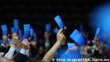 Hands hold up blue pieces of paper for the AfD (Getty Images/AFP/R. Hartmann)