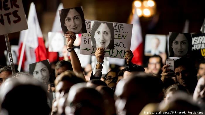 Protesters hold up signs with the murdered journalist's face in front of Joseph's Muscat office (picture-alliance/AP Photo/R. Rossignaud)