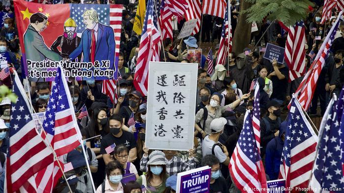 Багато демонстрантів тримає прапори США