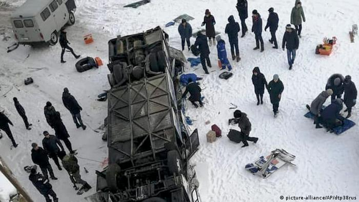People gather around an overturned bus on the frozen Kuenga River
