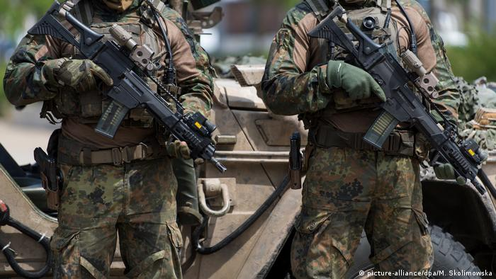 Soldiers with the German Special Forces Command pose with weapons