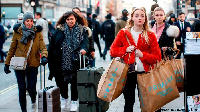 Drei jungen Frauen (zwei mit Rollkoffern, eine mehreren Plastiktüten) in der überfüllten Oxford Street in London in der Adventszeit