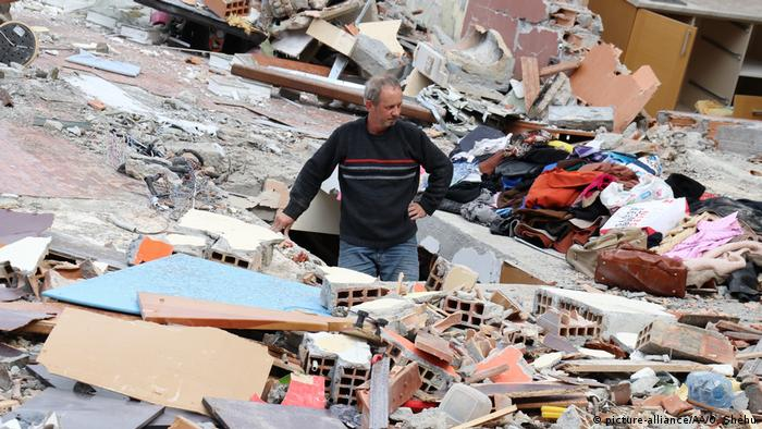 A man stands in the rubble of a collapsed building