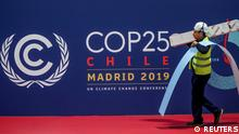 A worker walks past a COP 25 logo at IFEMA Convention Center, ahead of the 2019 U.N. climate change conference (COP 25) in Madrid