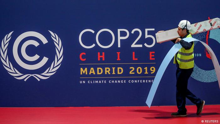 A worker walks past a COP 25 logo at IFEMA Convention Center, ahead of the 2019 U.N. climate change conference (COP 25) in Madrid (REUTERS)