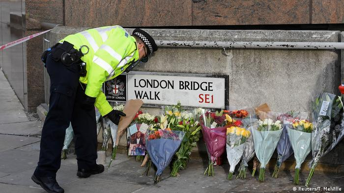 A police officer places a floral tribute near the scene of a stabbing on London Bridge (Reuters/T. Melville)