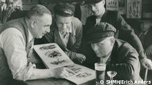 Christian Warlich showing tattoo flash book to sailors in a pub (SHMH/Erich Anders)