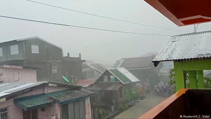 People walk as Typhoon Kammuri, known locally as Typhoon Tisoy, makes landfall
