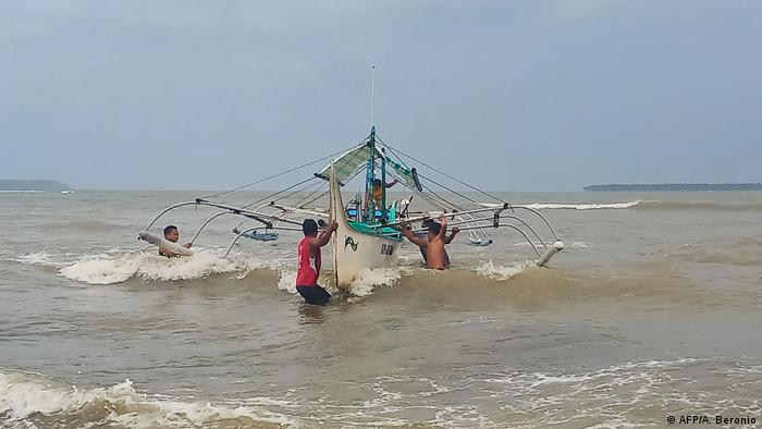 Residents help carry a wooden fishing boat into a secured area