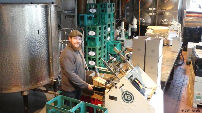Worker putting labels on bottles