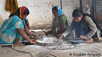Young girls cooking chapatis in an Indian village