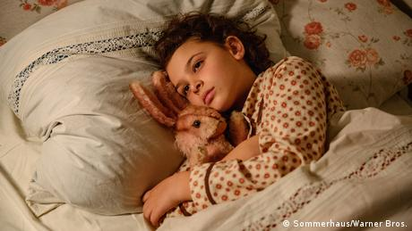 Film still When Hitler stole Pink Rabbit - a girl is seen lying in bed with a stuffed rabbit in her arms (Sommerhaus/Warner Bros.)