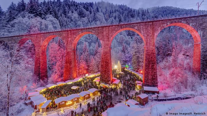 Germany - Christmas market at dusk covered in snow and festively lit in the Black Forest under a viaduct (Imago Images/A. Hettrich)
