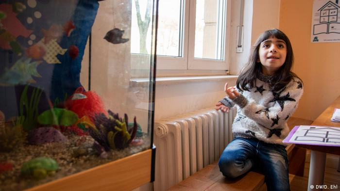 Azrin sits at a table next to a fish tank (DW/D. Ehl)