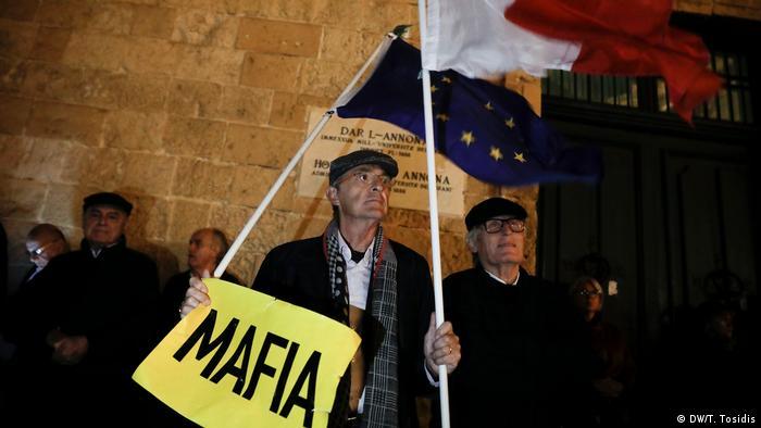 Demonstranten mit Malta- und EU-Flagge und einem Schils Mafia vor dem maltesischen Parlamentsgebäude