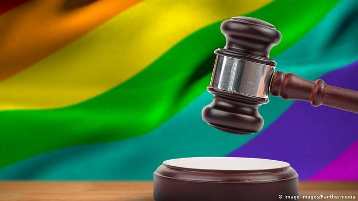 A hammer and gavel against a rainbow flag background