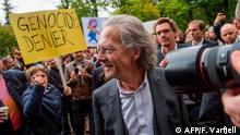 (FILES) In this file photo taken on September 21, 2014, a protester holds up a sign reading Genocide denier outside the Nationaltheatret in Oslo, as Austrian novelist and playwright Peter Handke arrives to be awarded with the International Ibsen Award 2014. - Peter Handke was awarded the 2019 Nobel Literature Prize on October 10, 2019. (Photo by Fredrik Varfjell / NTB SCANPIX / AFP)