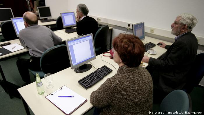 Adults on computers in a lesson