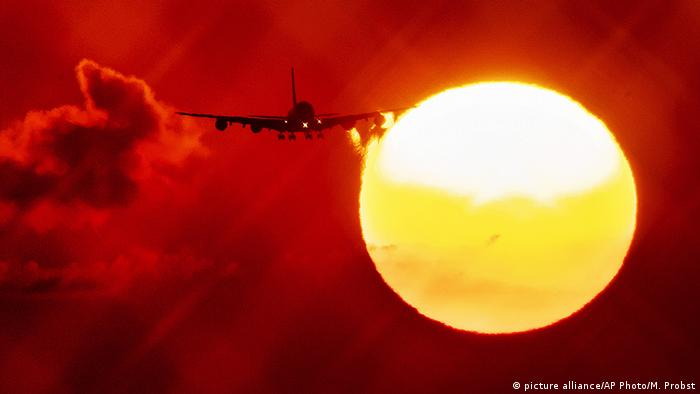 An aircraft passes the rising sun as it approaches the airport in Frankfurt, Germany (picture alliance/AP Photo/M. Probst)