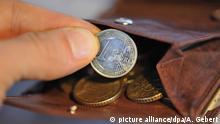 ARCHIV - ILLUSTRATION - Eine Hand nimmt am 22.01.2010 eine Euro-Münze aus einem Geldbörse, in dem sich weitere Münzen befinden. Mehrarbeit lohnt sich für Geringverdiener nicht immer. (zu dpa «Studie: Mehrarbeit rentiert sich für Geringverdiener nicht immer» vom 17.08.2017) Foto: Andreas Gebert/dpa +++(c) dpa - Bildfunk+++ | Verwendung weltweit