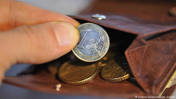 A person holds a euro coin