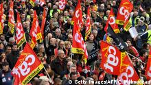 People wave the flags of French trade union General Confederation of Labour (CGT) as they take part in a demonstration to protest against the pension overhauls, in Marseille, southern France, on December 5, 2019 as part of a national general strike. - Trains cancelled, schools closed: France scrambled to make contingency plans on for a huge strike against pension overhauls that poses one of the biggest challenges yet to French President's sweeping reform drive. (Photo by CLEMENT MAHOUDEAU / AFP) (Photo by CLEMENT MAHOUDEAU/AFP via Getty Images)