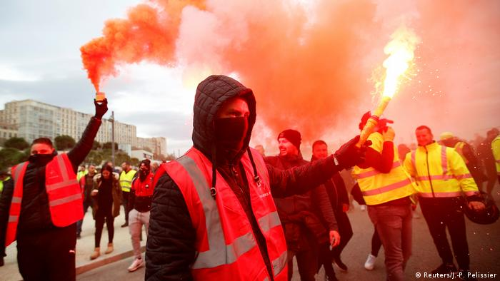 Protesters light red flares during the French general strike