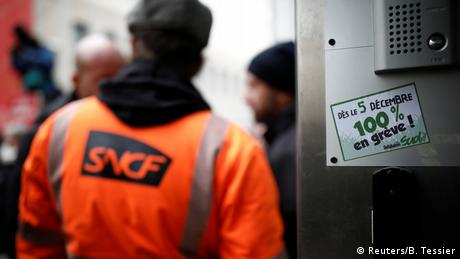 A rail worker wearing a fluorescent jacket with an SNCF train company logo on the back