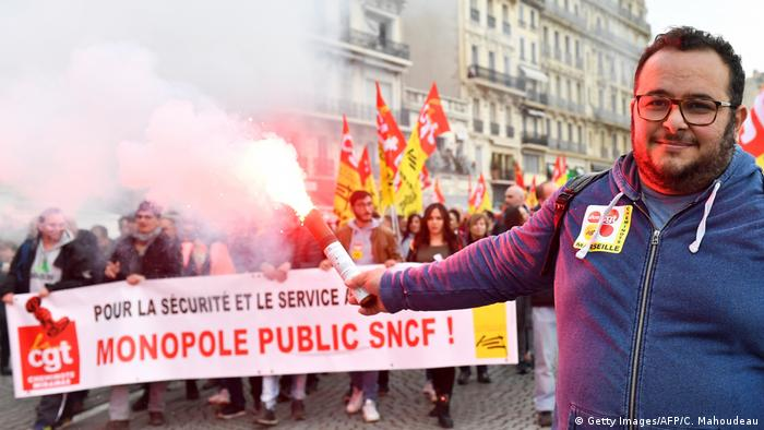 A man holds a flare in front of a CGT union banner