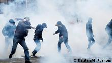 Masked protesters throw objects amid tear gas in Paris