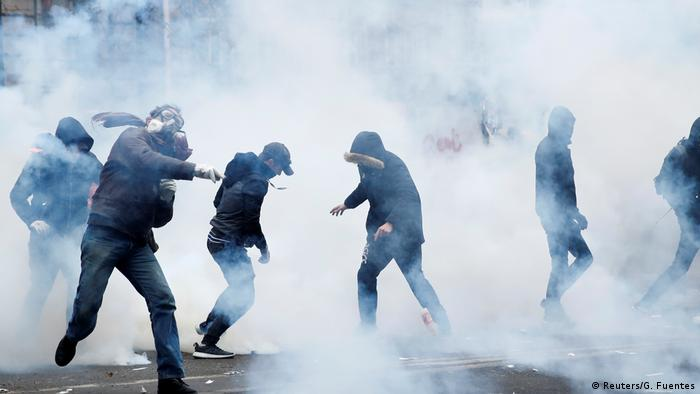Surrounded by tear gas, black-clad masked protesters throw objects in Paris during a national strike.