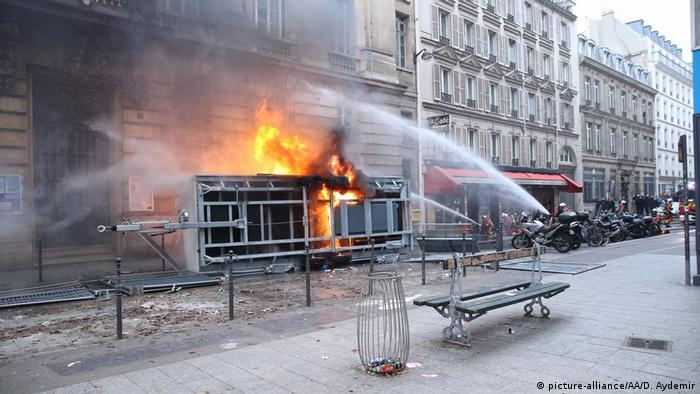 Firefights extinguish a blaze in a burning building in Paris during strikes of planned pension reforms
