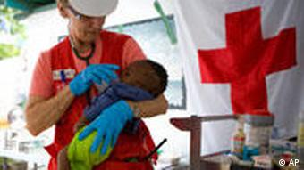 A female Red Cross worker holds a baby orphaned by the 2010 Haiti quake.