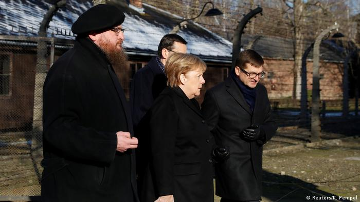 German Chancellor Angela Merkel, Poland's Prime Minister Mateusz Morawiecki and museum director Piotr Cywinski walk through the Arbeit Macht Frei gate at Auschwitz (Reuters/K. Pempel)