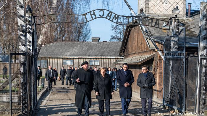 German Chancellor Angela Merkel, Poland's Prime Minister Mateusz Morawiecki and museum director Piotr Cywinski walk through the Arbeit Macht Frei gate at Auschwitz (picture-alliance/dpa/R. Michael)