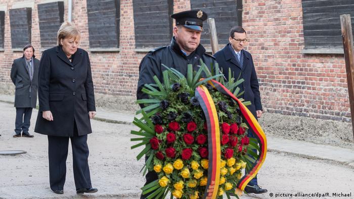 Merkel e o premiê polonês, Mateusz Morawiecki, com guarda que carrega coroa de flores
