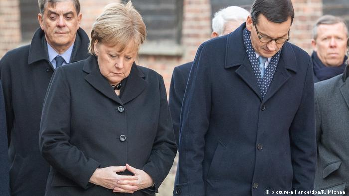 Merkel and Morawiecki bow their heads while at the Auschwitz death camp memorial (picture-alliance/dpa/R. Michael)