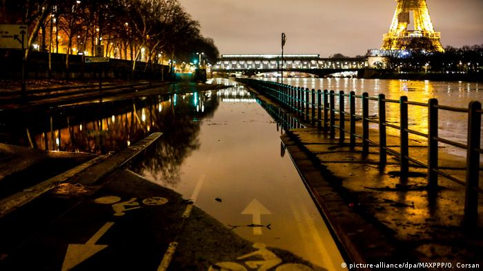 The banks of Seine in Paris, including a bike path, are seen flooded, with the Eiffel Tower in the background