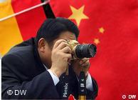 Ein Fotograf vor der chinesichen und der deutschen Flagge (Fotomontage: DW)