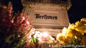 Beethoven's grave in Vienna at night, lit up and surrounded by flowers