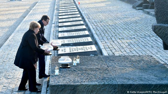 Merkel and Morawiecki place candles at the International Monument Auschwitz II-Birkenau during their visit at the former German Nazi death camp (Getty Images/AFP/J. MacDougall)