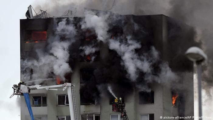 Firefighters on a ladder try to extinguish the flames after a gas explosion at the top of the apartment block